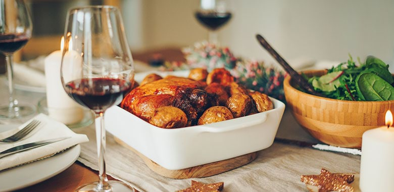 A festive table with a roast and wine glasses